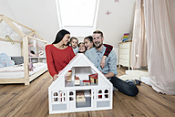 Happy family with three daughters sitting behind doll house in nursery - SBOF00613