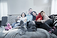 Happy parents and twin daughters on sofa in living room watching Tv - SBOF00616