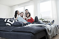 Family portrait of parents and twin daughters on sofa in living room - SBOF00628