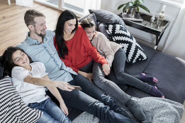 Happy parents and twin daughters on sofa in living room watching Tv - SBOF00631