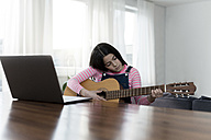 Girl playing guitar in front of laptop - SBOF00640