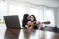 Mother kissing daugher playing guitar in front of laptop - SBOF00643