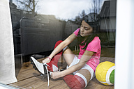 Girl putting on soccer shoes in front of living room window - SBOF00649