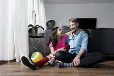Girl in soccer outfit sitting next to father on floor in living room - SBOF00652