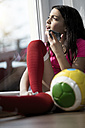 Girl in soccer outfit sitting on floor in living room speaking to someone on her smartphone - SBOF00655