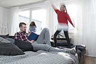 Girls jumping on sofa in living room while father reading a book - SBOF00658