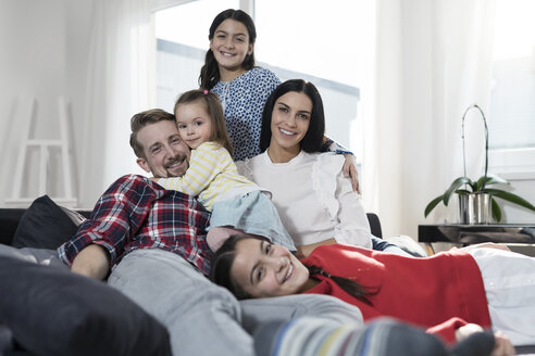 Portrait of parents and three daughers on sofa in living room - SBOF00664