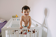 Portrait of happy baby girl in crib - GEMF01785