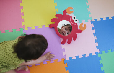 Cute baby girl looking at herself in a toy mirror on a colorful puzzle floor mat - GEMF01800