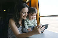 Happy mother and baby girl using smartphone while traveling by train - GEMF01806