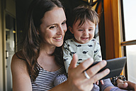 Happy mother and baby girl using smartphone while traveling by train - GEMF01809