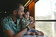 Father giving a cookie to his baby girl while traveling by train - GEMF01812