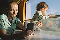 Father holding his baby girl and using smartphone while traveling by train - GEMF01815