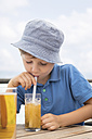 Boy blowing bubbles with staw in his soft drink - MIDF00852