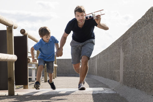Father and son running with toy plane - MIDF00858