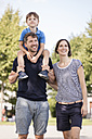 Happy family with father carrying son on shoulders - MIDF00861