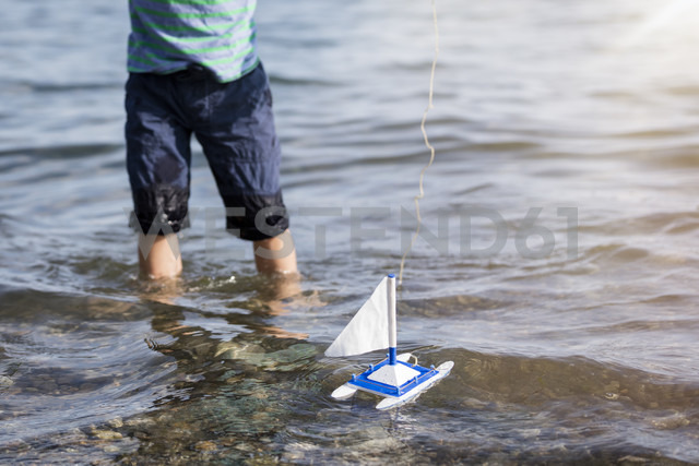 Boy playing with toy boat in water - MIDF00864 - Miriam Dörr/Westend61