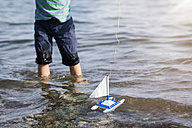 Boy playing with toy boat in water - MIDF00864