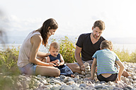 Germany, Friedrichshafen, Lake Constance, family playing with stones at lakeshore - MIDF00870