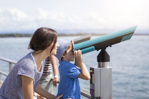 Germany, Friedrichshafen, Lake Constance, mother with son looking through telescope at lakeshore - MIDF00873