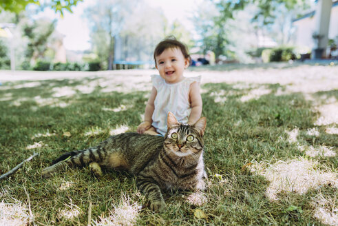 Portrait of tabby cat on a meadow with laughing baby girl sitting in the background - GEMF01817