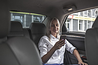 Smiling businesswoman checking cell phone in car - VPIF00038