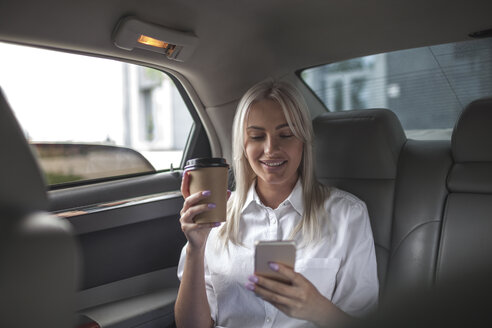 Smiling businesswoman with takeaway coffee and cell phone in car - VPIF00044