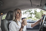 Smiling businesswoman holding takeaway coffee driving car - VPIF00050