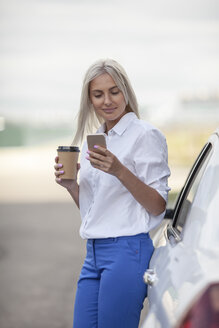 Smiling businesswoman with takeaway coffee and cell phone outside car - VPIF00053