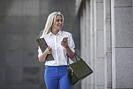 Smiling businesswoman with clipboard, handbag and cell phone on the move - VPIF00056