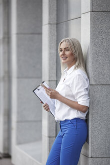Smiling businesswoman with clipboard and cell phone leaning against a wall - VPIF00059