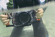 Man holding underwater DSLR camera case in a lake - MFF03924