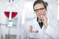 Scientist working in lab using beaker and pipet - ZEF14595