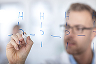 Scientist working in lab writing notes on glass pane - ZEF14601