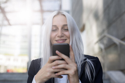Smiling young businesswoman checking cell phone in the city - GIOF03194
