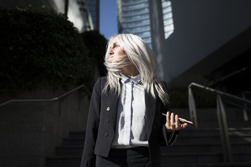 Young businesswoman with windswept hair in the city - GIOF03200