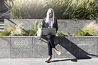 Young businesswoman sitting on a wall in the city using laptop - GIOF03206