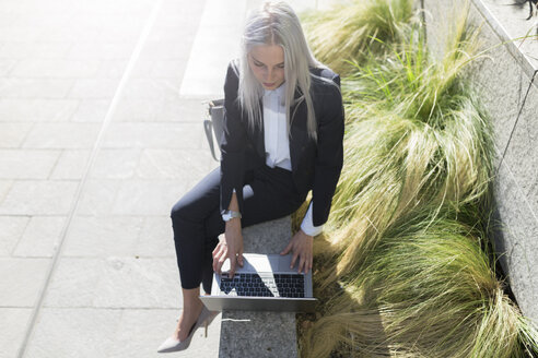 Young businesswoman sitting on a wall in the city using laptop - GIOF03209