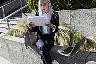 Young businesswoman sitting on a wall in the city with documents and laptop - GIOF03212