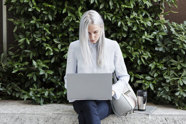Young businesswoman sitting on a wall in the city using laptop - GIOF03224