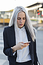 Young businesswoman checking cell phone in the city - GIOF03236