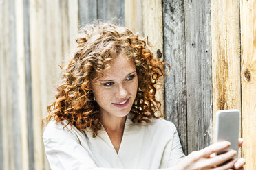 Portrait of smiling young woman taking selfie with cell phone in front of wooden wall - FMKF04475