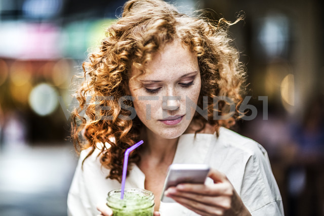 Portrait of young woman with beverage looking at cell phone - FMKF04478 - Jo Kirchherr/Westend61