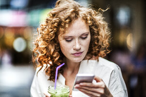 Portrait of young woman with beverage looking at cell phone - FMKF04478