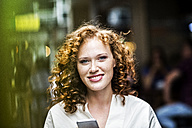 Portrait of smiling young woman with cell phone - FMKF04481