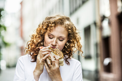 Portrait of young woman eating bagel outdoors - FMKF04487