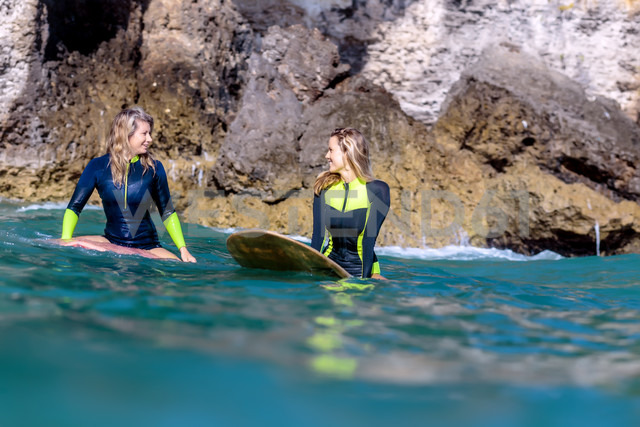 Indonesia, Bali, two smiling women on surfboards - KNTF00885