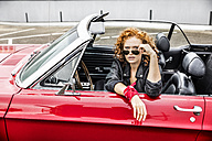 Portrait of redheaded woman wearing sunglasses in sports car - FMKF04495