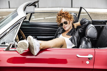 Portrait of redheaded woman wearing sunglasses in sports car - FMKF04498