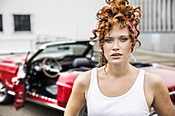 Portrait of redheaded woman at sports car - FMKF04501